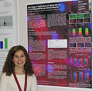 Student stands next to her symposium poster